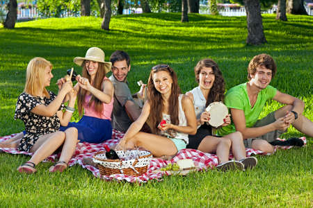 College students enjoying a picnic in the park sitting grouped together on rug on the grass laughing and joking amongst themselves