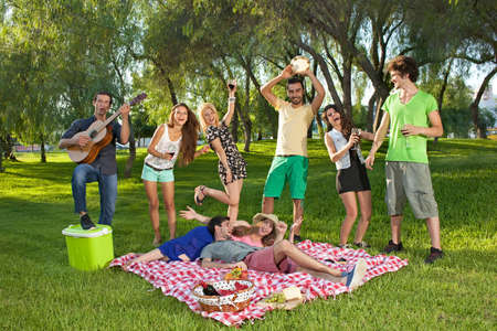 Lively group of teenagers in the park singing and dancing along to guitar music played by one of the boys as they enjoy a picnic outdoors