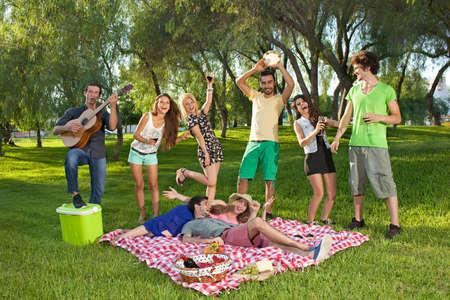 Levendige groep tieners in het park zingen en dansen mee met gitaar muziek gespeeld door een van de jongens als ze genieten van een picknick in openlucht