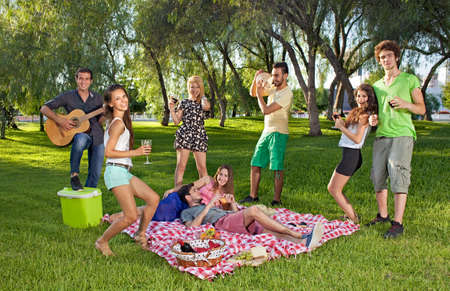 Group of lively happy teenage young friends enjoying a picnic outdoors dancing and singing along to guitar music played by one of the boys photo