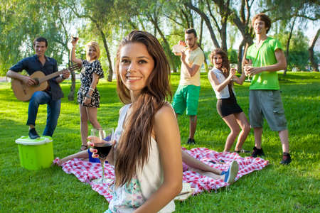Group of young college friends partying in the park with a pretty young teenage girl in the foreground smiling at the camera and holding a glass of red wine photo