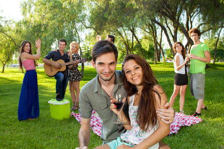 Affectionate young teenage couple sitting arm in arm on the grass in the park with a group of their friends playing guitar, dancing and partying photo