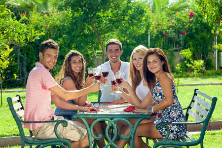 open air: Smiling teenagers celebrating the summer vacation sitting together at a wrought iron table at an open-air restaurant in a lush green garden smiling and toasting each other