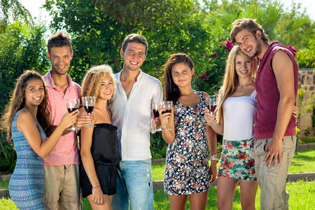 Group of happy confident young teenagers celebrating with glasses of red wine standing in a row in the garden smiling at the camera photo