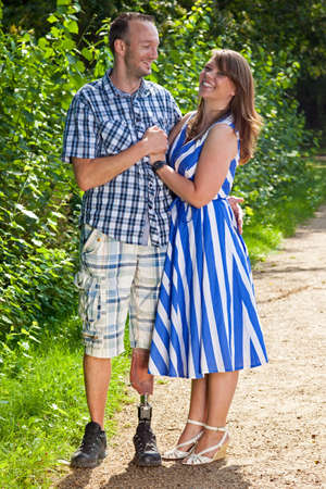 amputation: Happy attractive couple in love standing in a close embrace on a leafy green pathway with the man wearing a prosthetic leg following an amputation of his leg due to injury or disease
