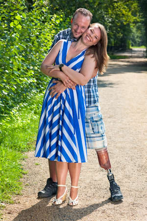 Disabled man wearing a prosthetic leg and an attractive stylish young woman standing on a gravel path in loving hug looking at the camera with happy smiles Stock Photo