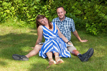 Happy attractive couple relaxing in the garden sitting close together on the grass with joyful friendly smiles - the man is disabled and is wearing a prosthetic artificial leg