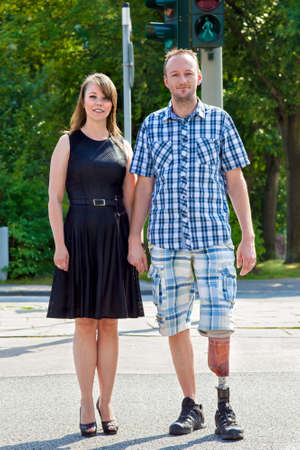 amputated: Confident handicapped man wearing an artificial limb having had one leg amputated standing hand in hand with an attractive woman in a street