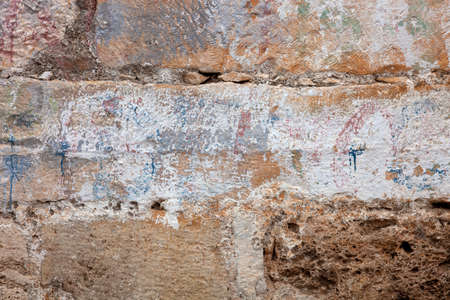 Antique Stonewall built from ashlars, close-up, with colored ornamentation by brush strokes  photo