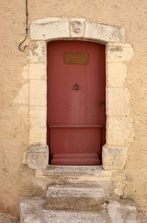 ornamente: Old restored red painted entrance door, with ancient steps in front, leading to an antique house  Provence, France  Stock Photo