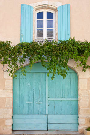 Wooden window and garage door with rounded top, turquoise painted, ivy tendrils among  France, Provence Stock Photo
