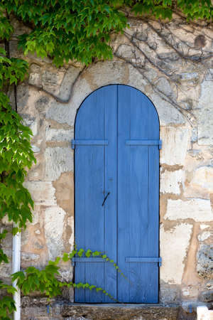ornamente: Old narrow door, blue painted in an ancient house block stone wall, surrounded by ivy tendrils  France, Provence