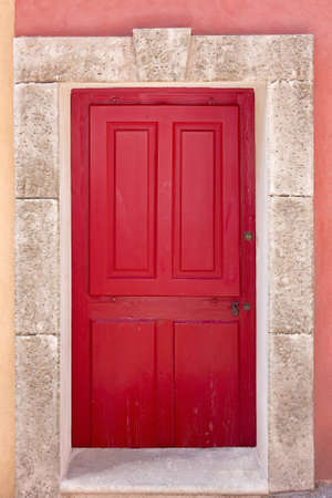 red door: Antique red coffered door, framed with rectangular block stones, wall is in the same color as door  France, Provence