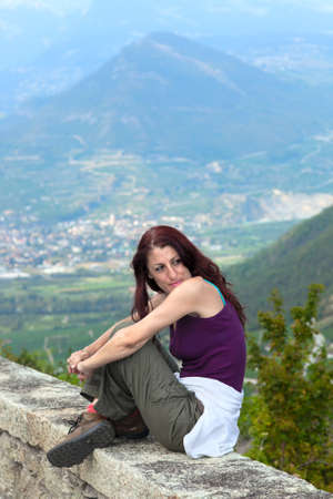 arms around: Woman wearing a tank top and pants,  indian sitting on a ledge overlooking the city, her arms around her knees  with mountains visible in the background
