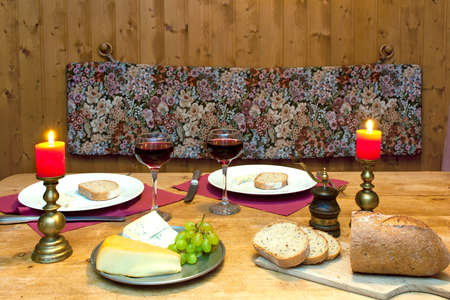 Intimate dinner table setting with candles and wine served in a romantic mountain chalet in the Alps