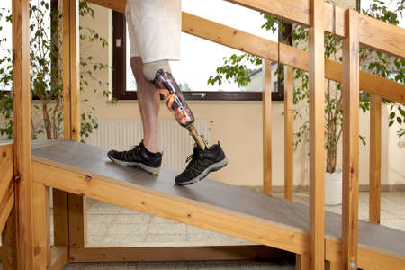medical distribution: Male prosthesis wearer training to climb a slope unaided in a speical parcour or interior area where surfaces have been laid out to simulate realistic environmental situations
