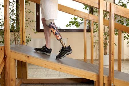 Man prothesedrager training om een helling zonder hulp in een speical parcour of interieur gebied waar oppervlakken zijn aangelegd om realistische ecologische situaties simuleren klimmen
