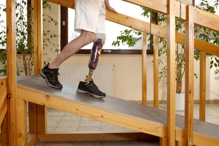 Male prosthesis wearer training to descend a slope in a speical parcour or interior area where surfaces have been laid out to simulate realistic environmental situations Stock Photo
