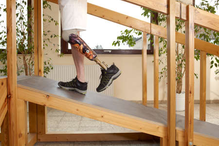 Male prosthesis wearer training to walk uphill on a wooden slope in a speical parcour or interior area where surfaces have been laid out to simulate realistic environmental situations Stock Photo - 24681336