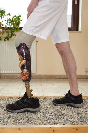 Male prosthesis wearer learning to transfer his weight on uneven surfaces in a special parcour or interior area where surfaces have been laid out to simulate realistic environmental situations