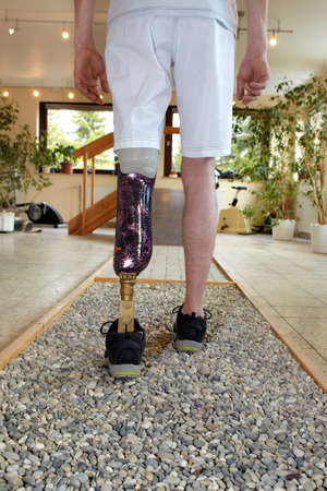 wearer: Male prosthesis wearer with lower leg amputation training to walk on loose stones in a special parcour or interior area where surfaces have been laid out to simulate realistic environmental situations