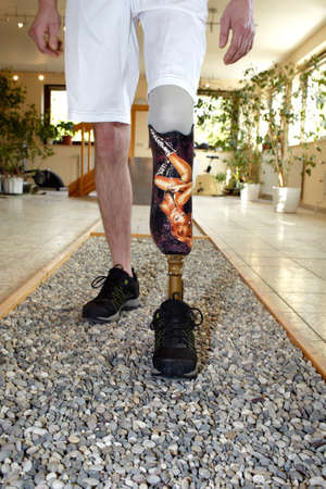 wearer: Male prosthesis wearer learning to walk in a speical parcour or interior area where surfaces have been laid out to simulate realistic environmental situations