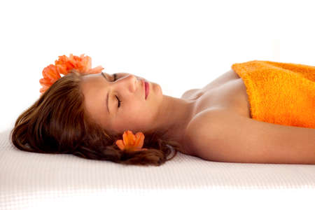 draped: Beautiful young woman in a state of total relaxation and wellbeing lying with her eyes closed on a spa table draped in an orange towel with orange blossoms in her hair