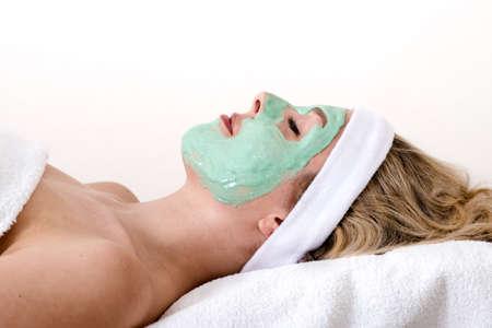 thalasso: Belle femme blonde jouit d'une boue verte soins de beauté du visage dans un salon, portant les yeux fermés détendue et avec un fond blanc