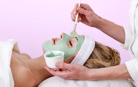 thalasso: Esthéticienne appliquer un masque Esthéticienne visage thalasso application d'un masque de visage à partir d'un petit récipient à une belle femme dans un centre de soins