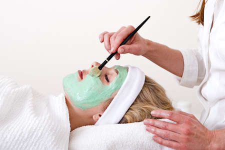 thalasso:  Beautician applying green thalasso facial mask with a brush on the cheekbones of a laying and relaxed beautiful blond woman against a white background