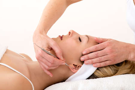 homeopath: Homeopath using ear acupuncture techniques  Alternative practitioner using ear acupuncture techniques  also called auriculotherapy  on the ear of a beautiful blond woman Stock Photo