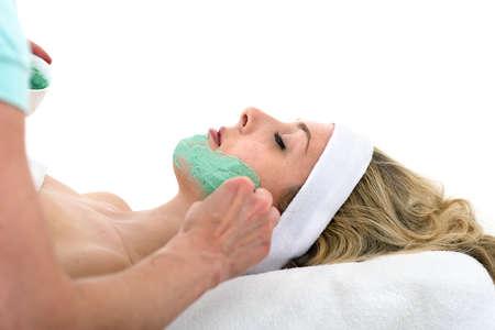 thalasso: Esthéticienne appliquer le masque facial sur belle femme Esthéticienne appliquer verte masque facial thalasso sur la joue de la maçonnerie et détendue belle femme blonde sur un fond blanc