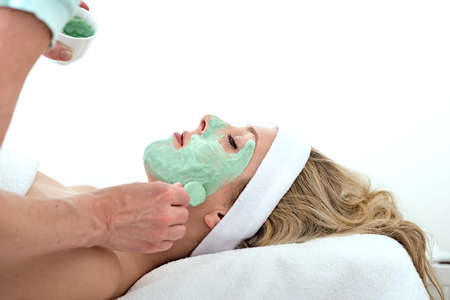 beautician:  Beautician applying green thalasso facial mask with a brush on the cheek of a laying and relaxed beautiful blond woman against a white background Stock Photo