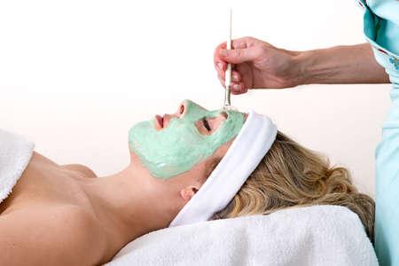 thalasso: Esthéticienne appliquer verte masque facial thalasso avec un pinceau sur le front de la maçonnerie et détendue belle femme blonde sur un fond blanc Banque d'images