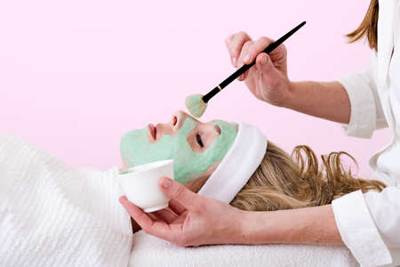 thalasso: Beautician applying green thalasso facial mask using a brush and a cup on the nose of a laying and relaxed beautiful blond woman against a pink background Stock Photo