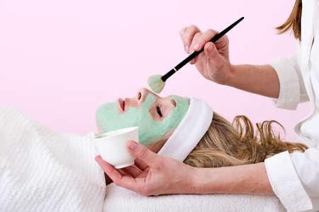 thalasso: Esthéticienne appliquer verte masque facial thalasso aide d'une brosse et une tasse sur le nez de la maçonnerie et détendue belle femme blonde sur un fond rose Banque d'images