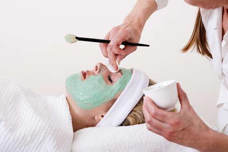 thalasso: Esthéticienne retoucher le masque facial vert sur le sourcil d'une pose détendue et belle femme blonde, tout en tenant un pinceau et une tasse sur un fond blanc
