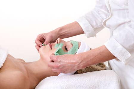 thalasso: Esthéticienne décoller la beauté verte masque facial sur une pose détendue et belle femme blonde sur un fond blanc Banque d'images
