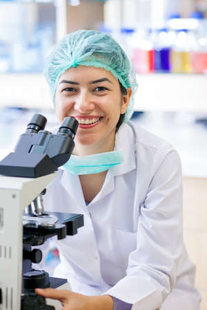 warmly: Happy female laboratory technician sitting at her microscope in a surgical cap and mask looking up to smile warmly at the camera