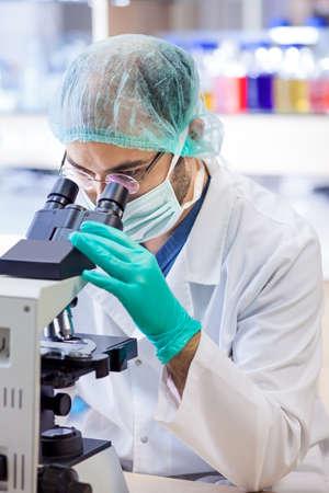 化学実験室の分析のためのスライドで彼の顕微鏡の眼を見ての仕事で男性の科学者
