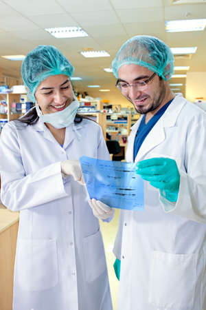 protective: Two laboratory technicians smiling as they study the results of an experiment or test, looking at the tracing which they are holding in their gloved hands