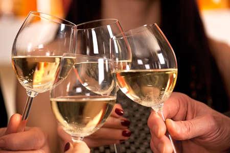 sektglas: Klirrend Gläser mit Weißwein und Toasten.