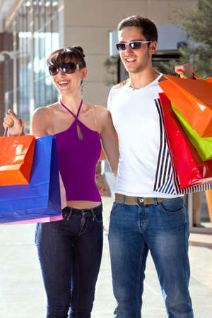 Happy young couple embracing each other, having fun and laughing, carrying colorful shopping bags  photo