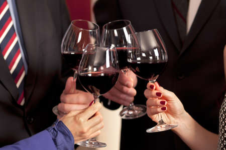 Clinking glasses and toasting with red wine in celebration. Stock Photo