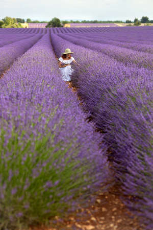 longshot: Pretty woman in white dress sitting in floral field of lavender, enjoying lavender flowers, picking some purple twigs  Placed in the middle ground  Sky visible  Long-shot