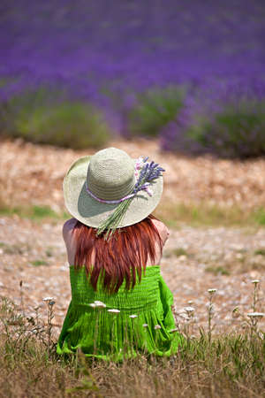 flowering field: Romantic lady wearing green dress and hat, sitting in front of violet lavender field  Close, back-view  The hat is decorated with lavender twigs  Stock Photo
