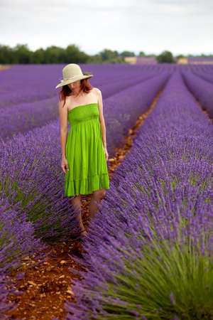 somnolent: Beautiful female in green dress and hat standing in lavender field  Her head is turned slightly to the right, looking dreamy downwards at the violet flowers  Background blurry  Stock Photo