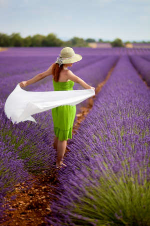 lavender bushes: Attractive woman in green dress in lavender field holding long white scarf  Wearing light green hat, decorated with lavender flowers  Blue sky  Summer concept  Stock Photo