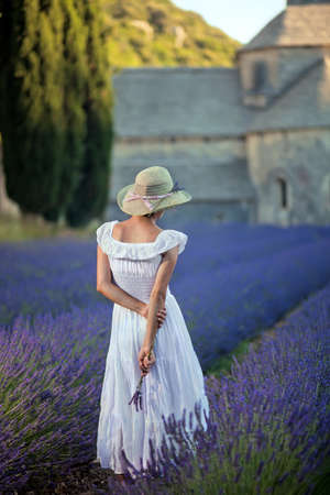 lavender bushes: Romantic lady in lavender field  An ancient monastry in background  Wearing white dress and light green hat, holding some lavender twigs in her hand  Relaxing and enjoying  Stock Photo