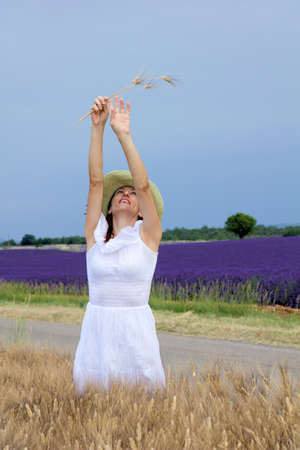 lavender bushes: Cheerful lady standing in cornfield, stretches her arms upwards, holding some ears of wheat  In the background purple lavender field